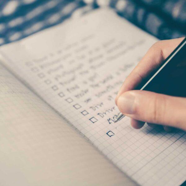 Eine Person schreibt eine To-Do-Liste.