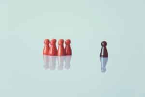 Eine einzelne schwarze Spielfigur steht getrennt von einer Gruppe roter Spielfiguren.