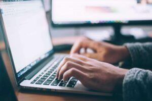 Eine Personen arbeitet an einem Laptop.