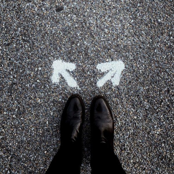 Eine Person steht vor Pfeilen die auf den Boden gemalt sind und in utnerschiedliche Richtungen weisen.