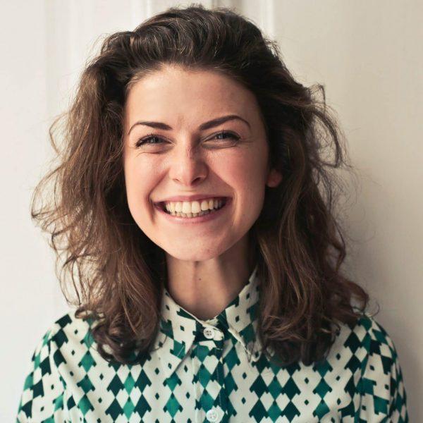 Eine Person lächelt freudestrahlend in die Kamera.