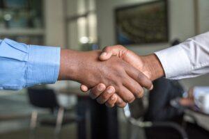 Zwei Personen geben sich die Hand.