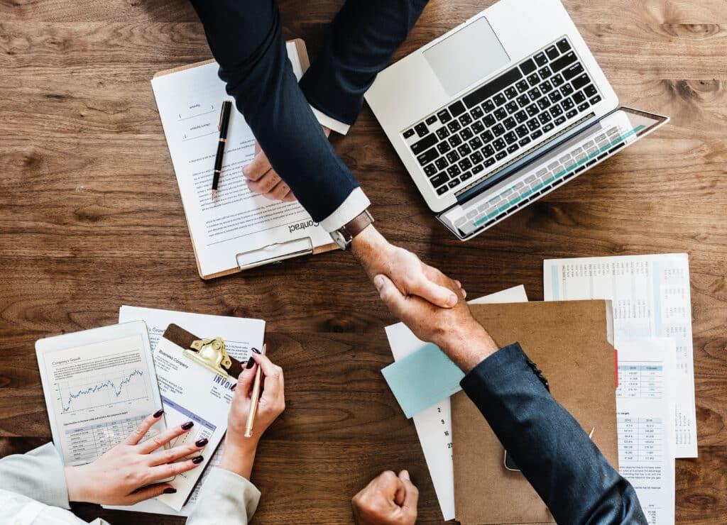 Drei Personen sitzen an einem Tisch und führen Vertragsverhandlungen. Zwei Personen geben sich die Hand.