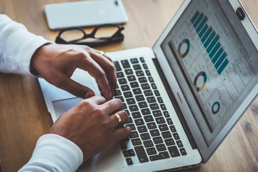 Eine Person betrachtet Diagramme auf einem Computerbildschirm.