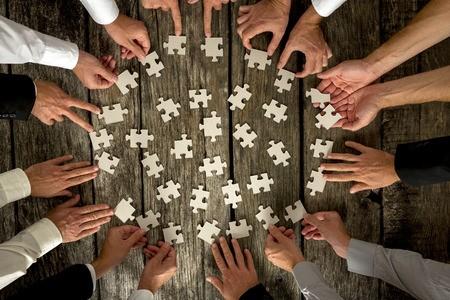 Viele Personen setzen gemeinsam ein Puzzle zusammen.