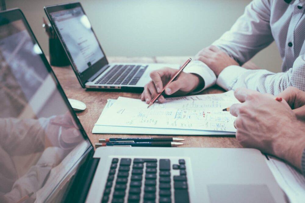Zwei Personen sitzen an einem Tisch und besprechen Entwürfe auf Papier.