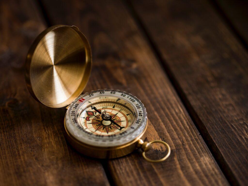 Ein aufgeklappter goldener Kompass liegt auf einem alten Holztisch.