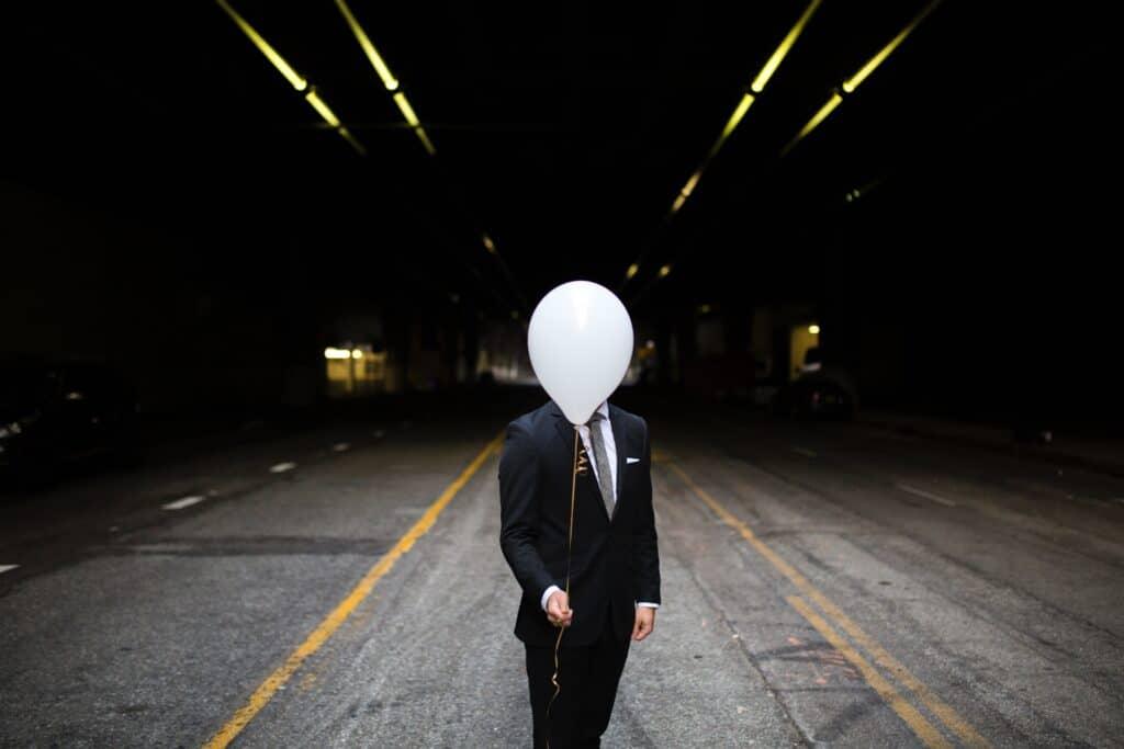 Eine Person versteckt ihr Gesicht hinter einem Luftballon