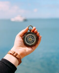 Eine Person hält einen Kompass in die Luft. Im Hintergrund ist das Meer zu sehen.