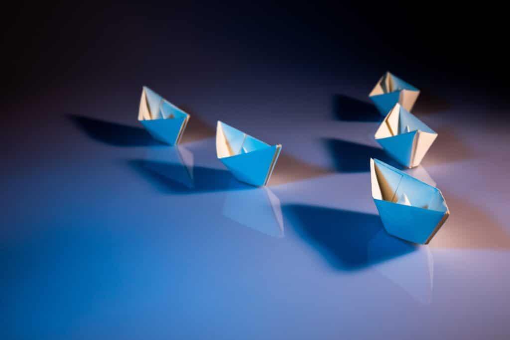 Papierschiffe in V-Formation auf einer gläsernen Oberfläche