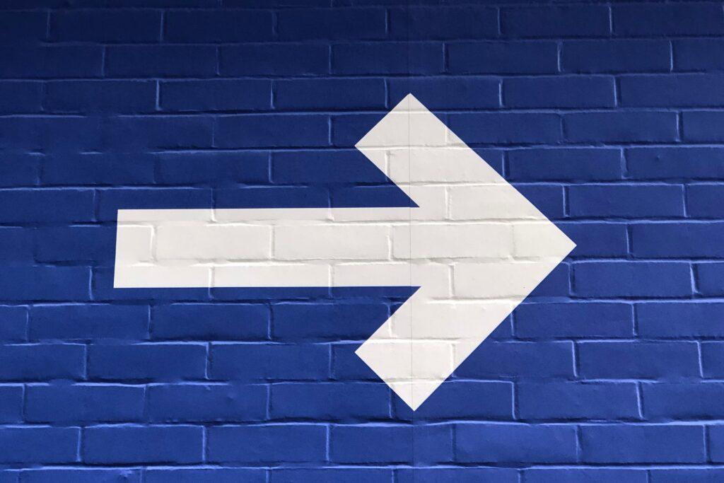Ein fetter weißer Pfeil nach rechts auf einer blauen Ziegelwand