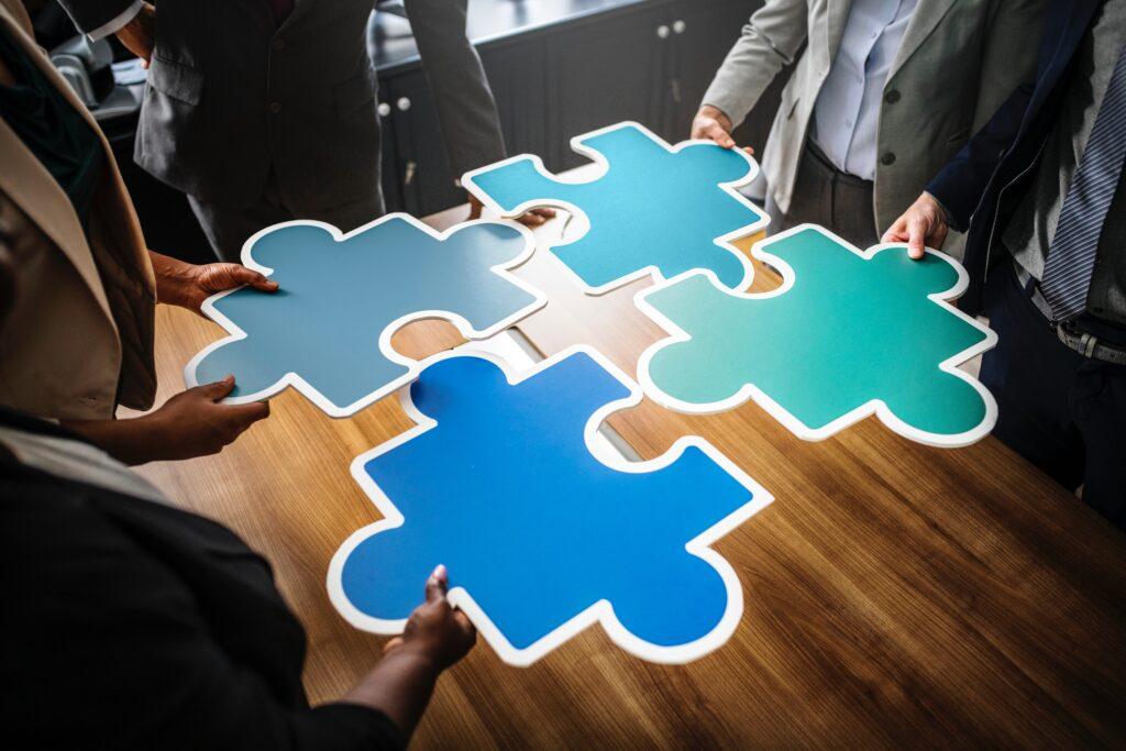 Vier Personen setzen ein überdimensionales Puzzle zusammen.